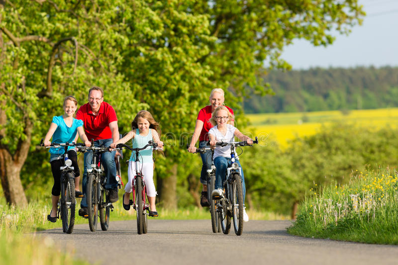 Family with kids cycling in summer with bicycles. Family with three girls having a weekend excursion on their bikes or bicycles on a summer day in beautiful royalty free stock image