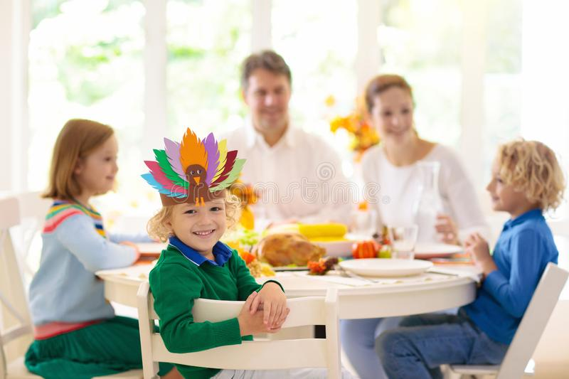 Family with kids at Thanksgiving dinner. Turkey royalty free stock images