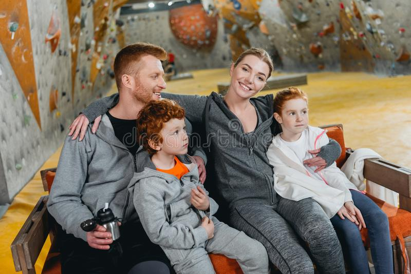 A family with kids at gym sitting and relaxing on a bench with climbing walls. In the background stock images