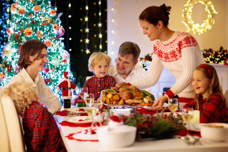 Family with kids having Christmas dinner at tree stock photo