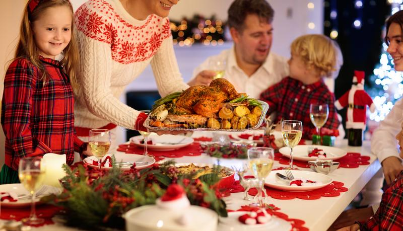 Family with kids having Christmas dinner at tree royalty free stock images