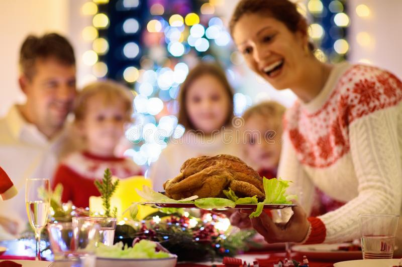 Family with kids having Christmas dinner at tree royalty free stock image