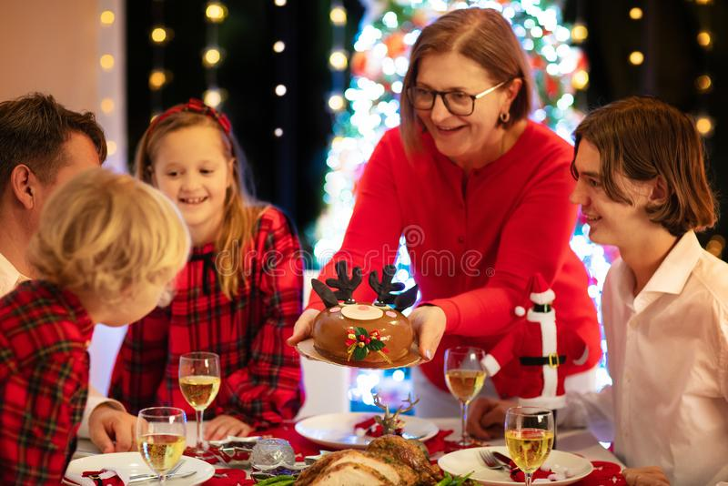 Family with kids having Christmas dinner at tree royalty free stock photo