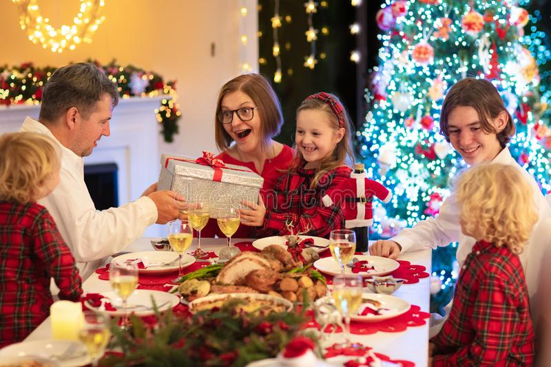Family with kids having Christmas dinner at tree stock image