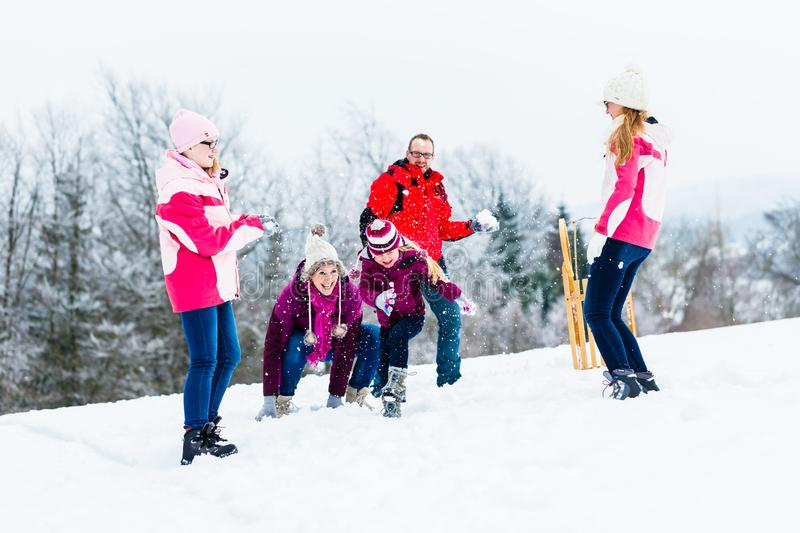 Family with kids having snowball fight in winter royalty free stock image