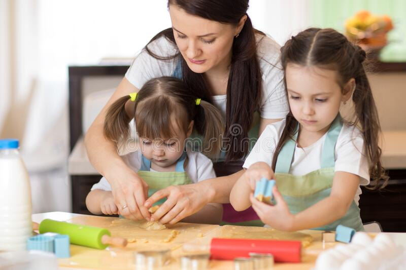 Family kids and mother baking cookies in kitchen together royalty free stock image