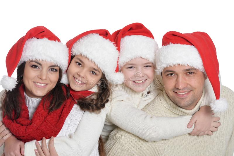 Portrait of family with kids in santa hats. Family with kids in Santa hats posing on white background royalty free stock photos
