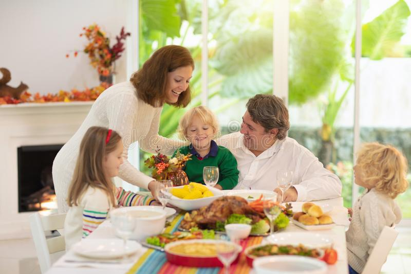 Family with kids at Thanksgiving dinner. Turkey stock image