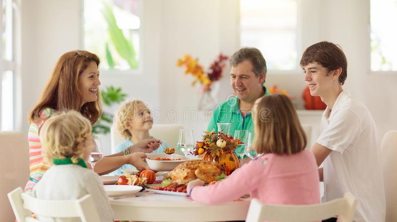 Family with kids at Thanksgiving dinner. Turkey royalty free stock photography