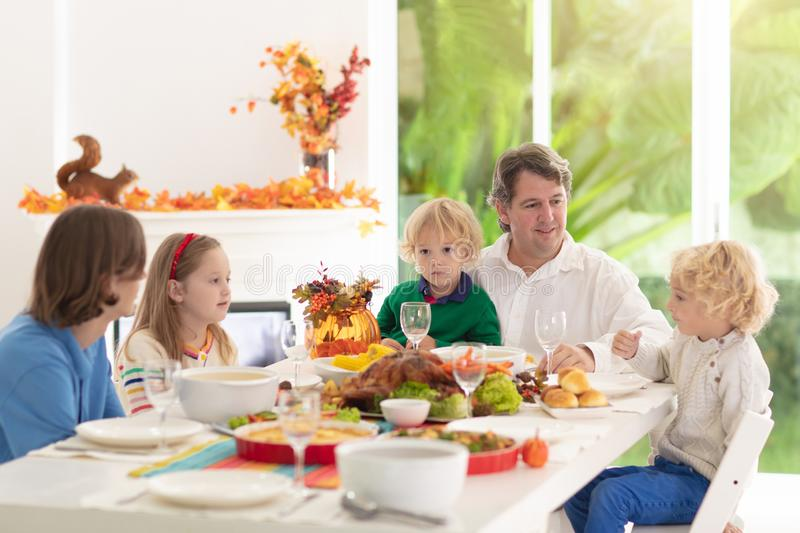 Family with kids at Thanksgiving dinner. Turkey royalty free stock image