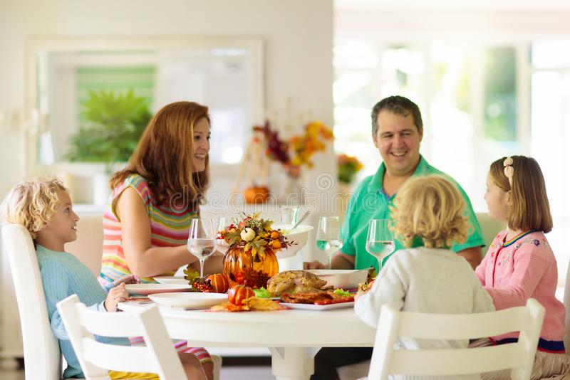 Family with kids at Thanksgiving dinner. Turkey stock images