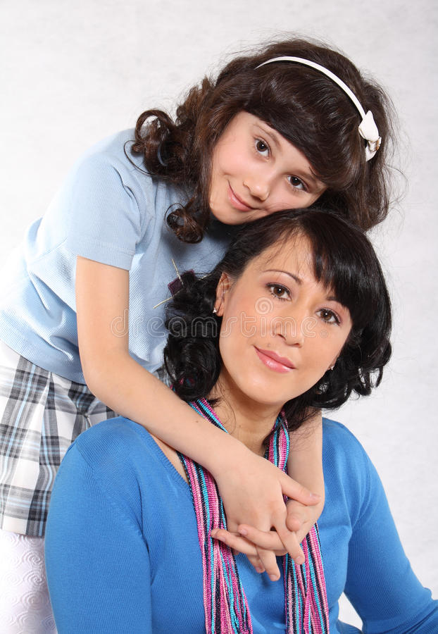 Family kind attitudes. Portrait of mum and the daughter on a light background royalty free stock images