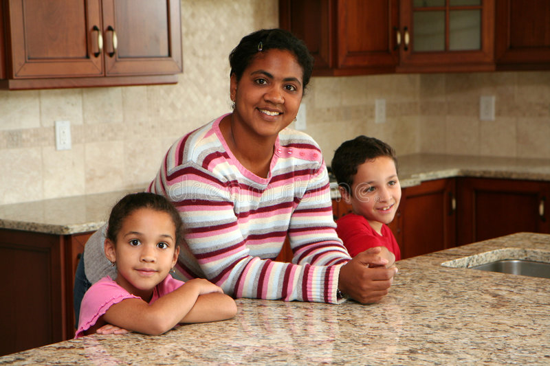 Family In Kitchen. A hispanic family stands in a luxury home kitchen royalty free stock photos