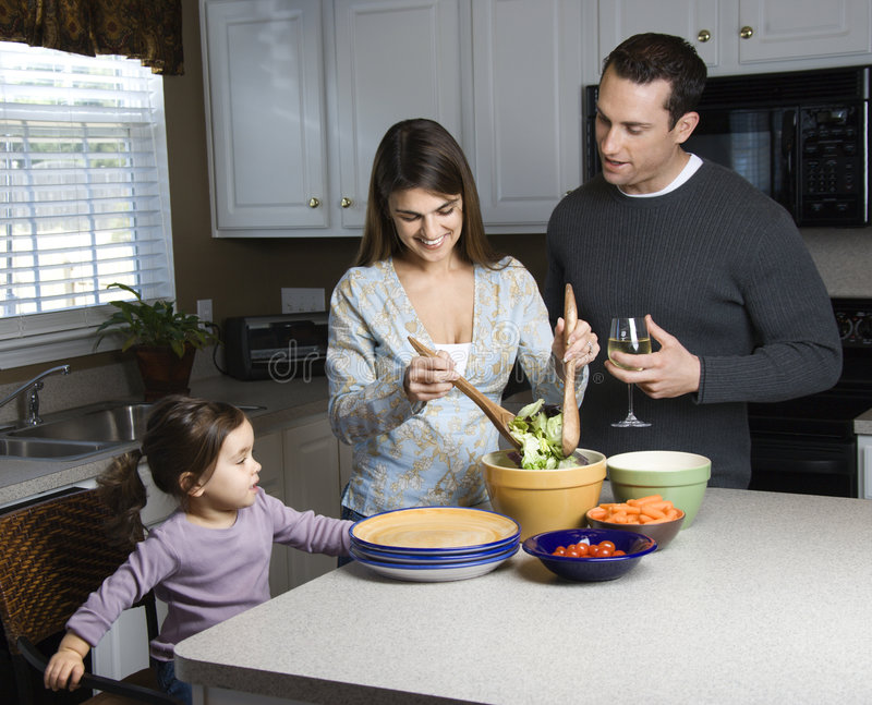 Family in kitchen. Caucasian woman making salad on kitchen counter with daughter and husband