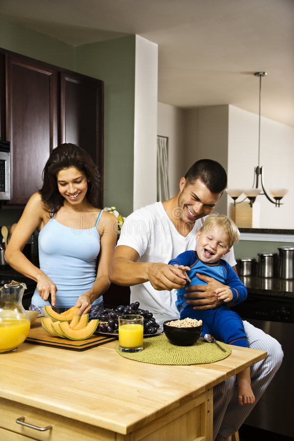 Family in kitchen. Caucasian family with toddler in kitchen at breakfast stock images