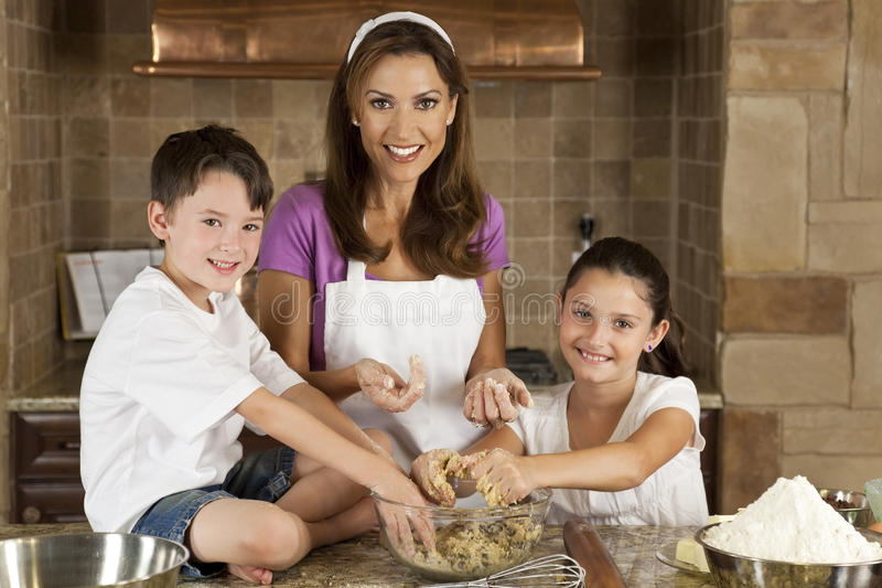 Family In Kitchen Cooking & Baking Making Cookies. An attractive smiling mother, son and daughter family cooking and baking chocolate chip cookies in a kitchen royalty free stock photography