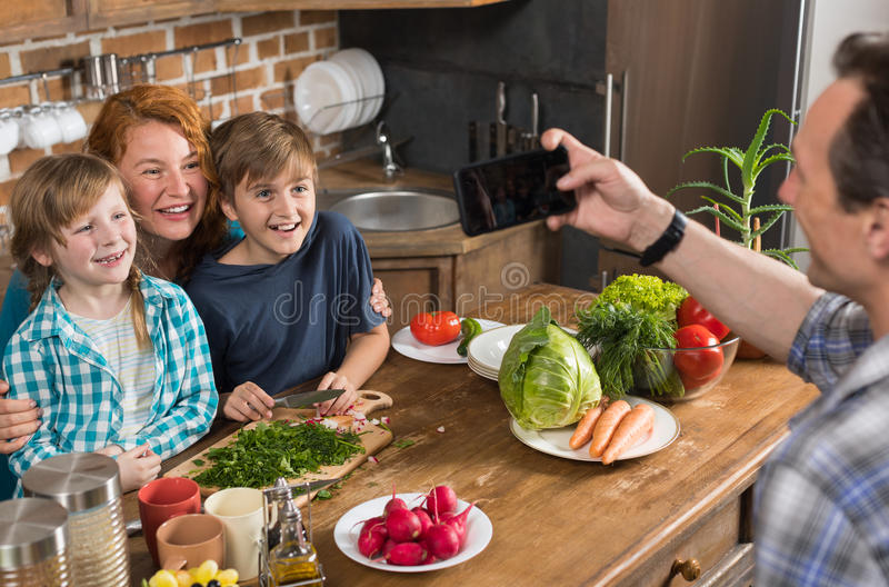 Family In Kitchen Cooking Food Father Taking Photo On Cell Smart Phone Of Mother Son And Daughter Sitting At Table stock photo