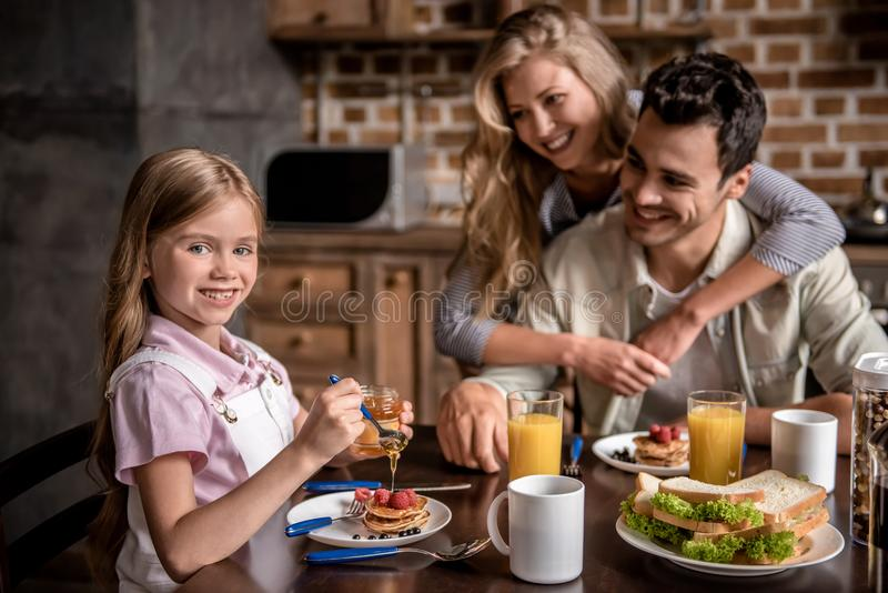 Family in kitchen. Happy family having breakfast in kitchen. Girl is adding honey to the pancakes while parents are looking at her and smiling stock image