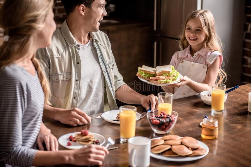 Family in kitchen. Happy family having breakfast in kitchen. Little girl is bringing sandwiches to her parents and smiling royalty free stock image