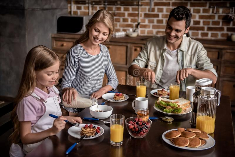 Family in kitchen. Happy family are talking and smiling while having breakfast together in kitchen royalty free stock image