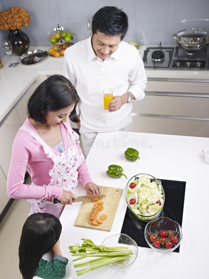 Family in kitchen. High angle view of an asian family preparing meal in kitchen stock images