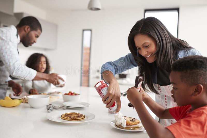 Family In Kitchen At Home Making Pancakes Together stock image