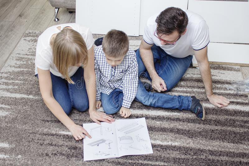 Family is kneeling on a beige carpet. In front of them is a furniture assembly manual, which they read with great care. stock images