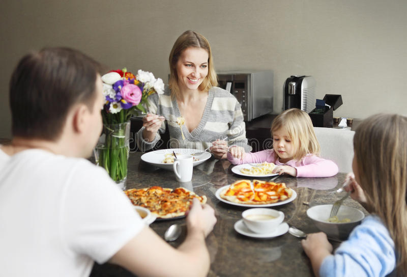 Family laughing around a good meal in kitchen royalty free stock photography