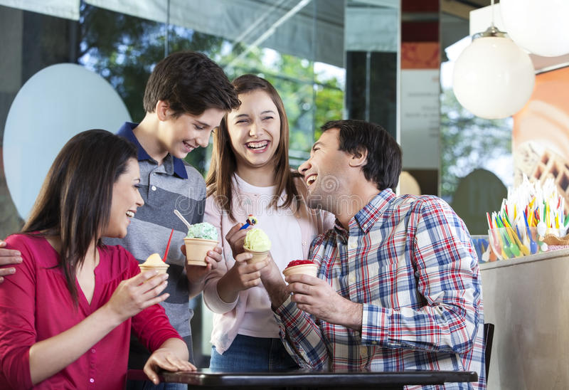 Family Laughing While Having Ice Creams In Parlor stock images