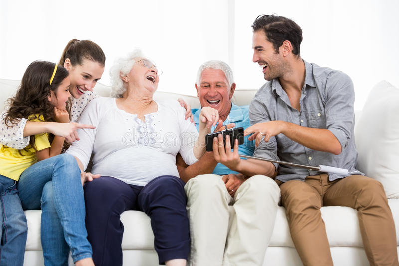 Family laughing while looking at smartphone photos stock image