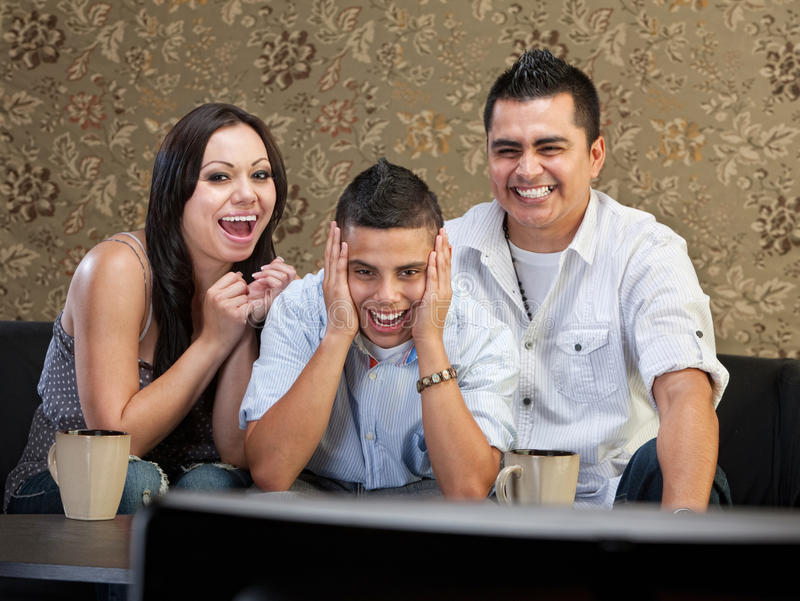 Family Laughing at TV. Happy family of three laughing at a television royalty free stock images