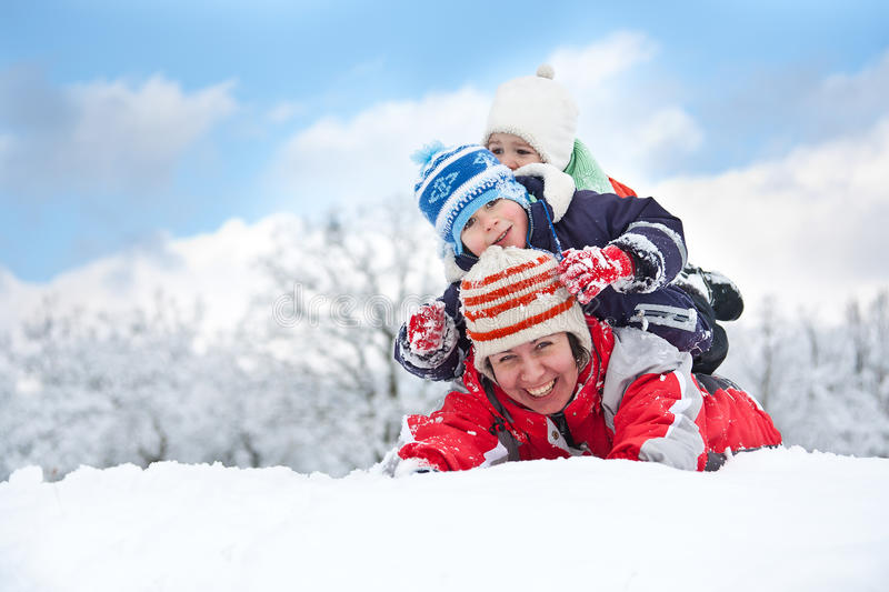 Family laying down in the snow stock photography