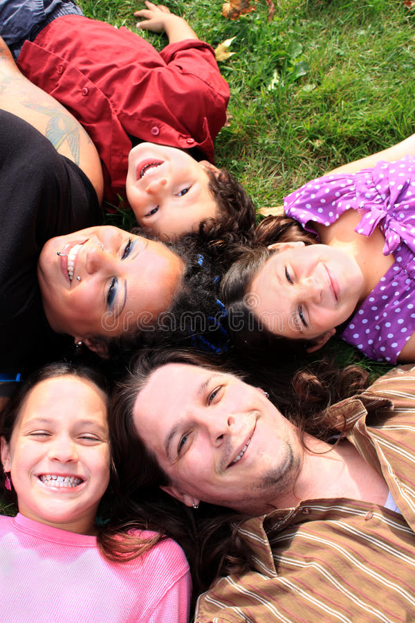 Family laying on the grass. Attractive muti-racial family laying on the grass smiling and having fun royalty free stock photos