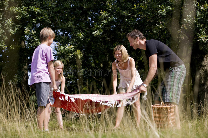 A family laying a picnic blanket on the grass stock images