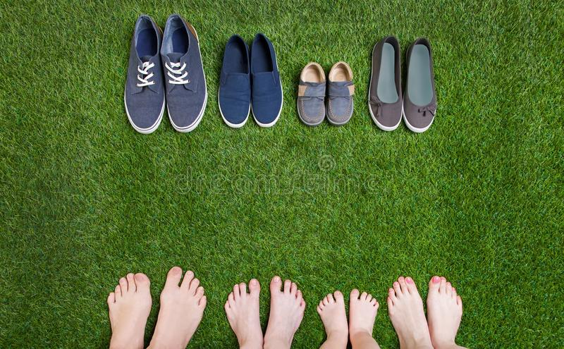 Family legs and shoes standing on green grass. Family legs standing on green grass having fun outdoors in spring park with theirs shoes royalty free stock photo
