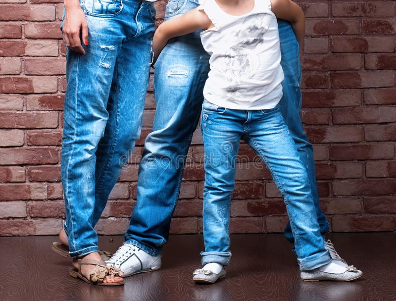 Family legs wearing blue jeans. People against brick wall royalty free stock photo