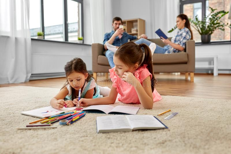Happy sisters drawing and doing homework at home stock photos