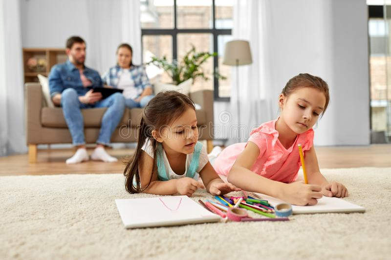 Happy sisters drawing in sketchbooks at home royalty free stock images