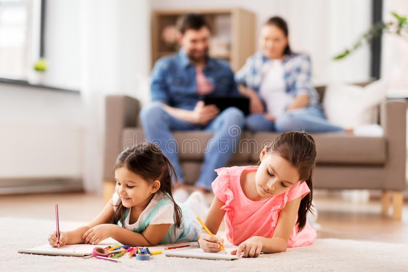 Happy sisters drawing in sketchbooks at home stock photography