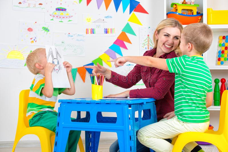 Children with mom and draw pictures in the kids room. Family leisure.Children with mom and draw pictures in the kids room royalty free stock photography