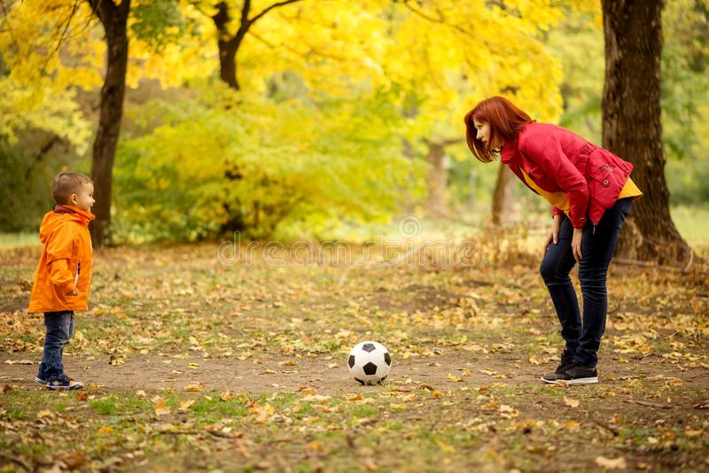 Family leisure outdoors: little boy playing football with mother in autumn park stock photography
