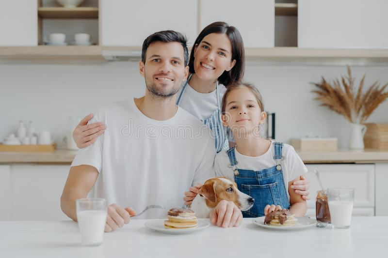 Family, leisure, pastime, eating concept. Father, mother and daughter, jack russell terrier dog pose all together at camera royalty free stock photos