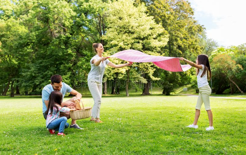 Family laying down picnic blanket in summer park. Family, leisure and people concept - happy mother with daughter laying down picnic blanket on grass in summer stock photo