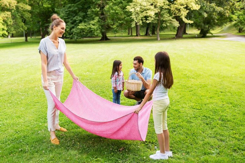 Family laying down picnic blanket in summer park royalty free stock images