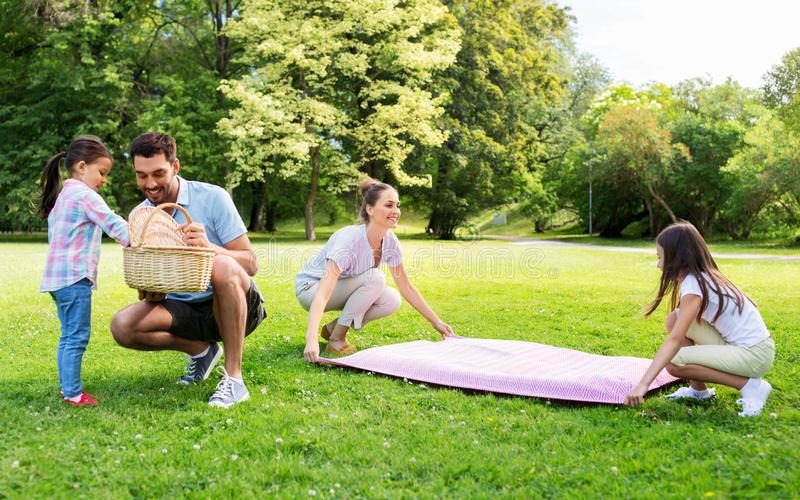 Family laying down picnic blanket in summer park royalty free stock photo