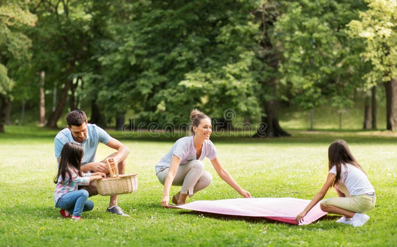 Family laying down picnic blanket in summer park stock photos