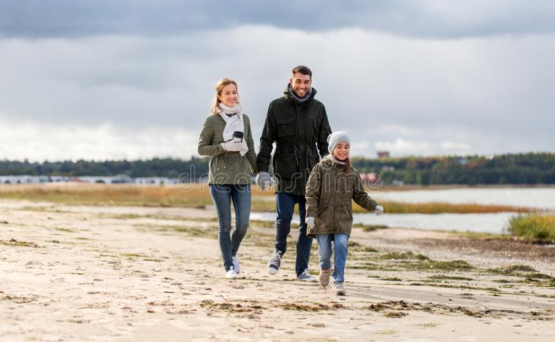 Happy family walking along autumn beach stock images