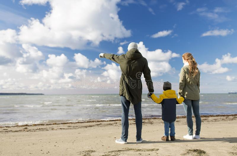 Happy family at autumn beach looking at sea royalty free stock images