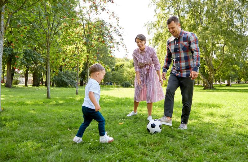 Happy family playing soccer at summer park royalty free stock photo