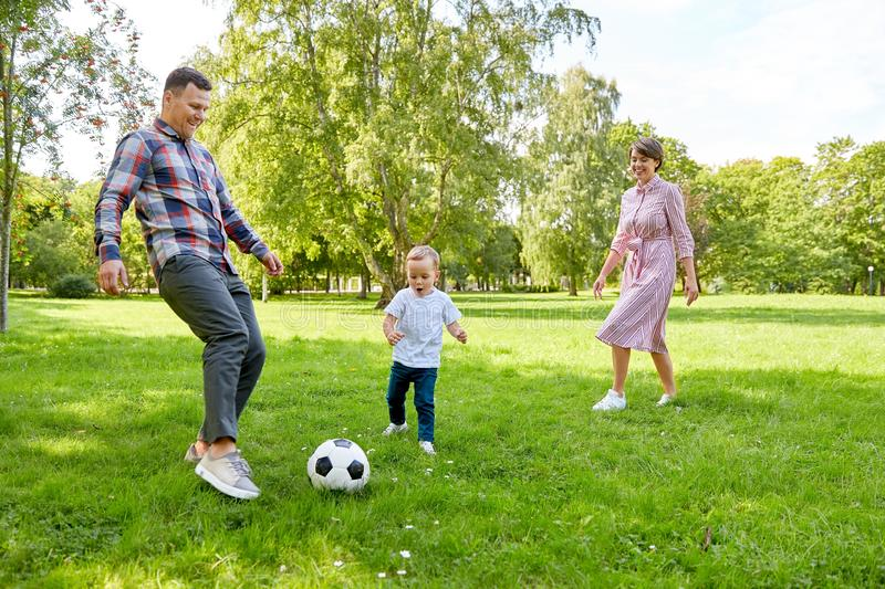 Happy family playing soccer at summer park royalty free stock photography